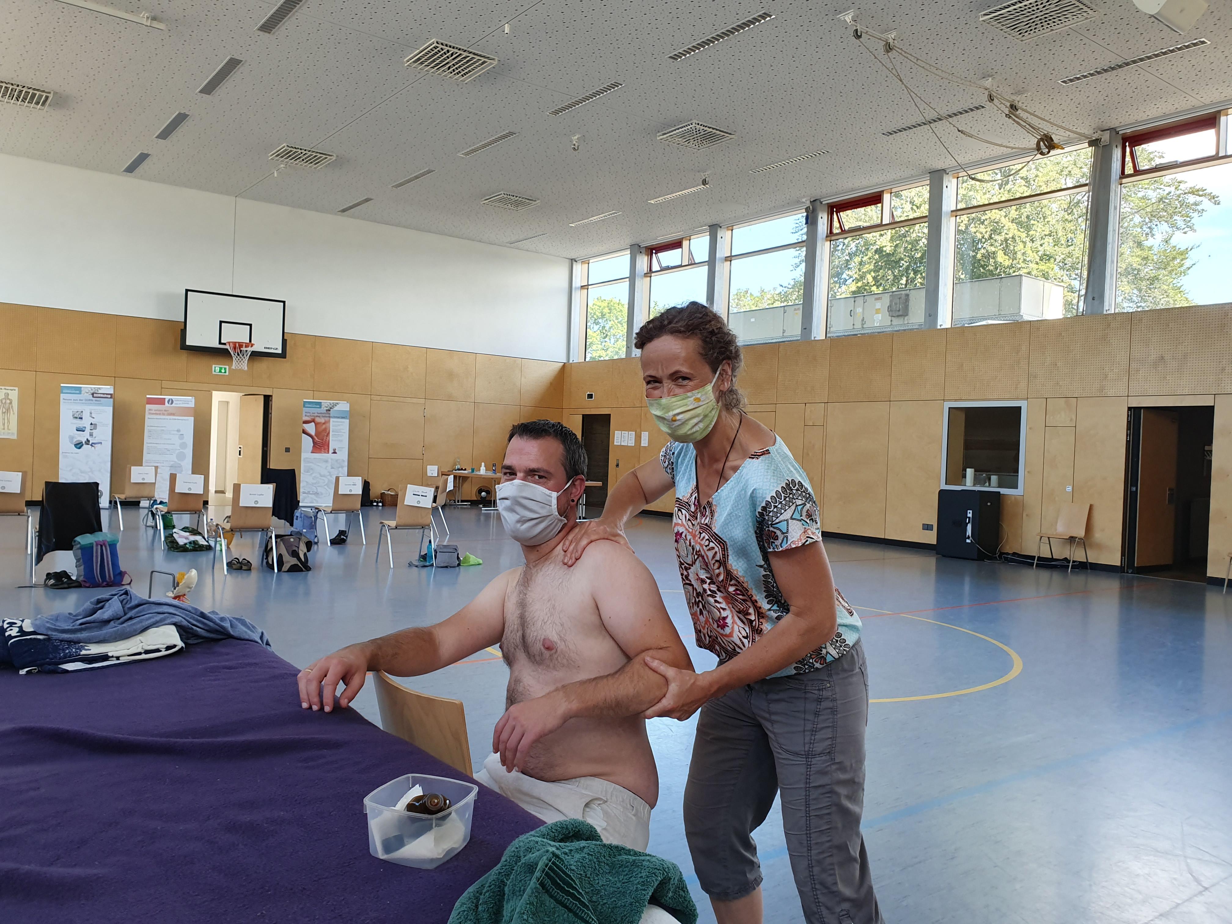 Eine Frau mit Mund- und Nasenschutz behandelt die Schulter eines Seminarteilnehmers